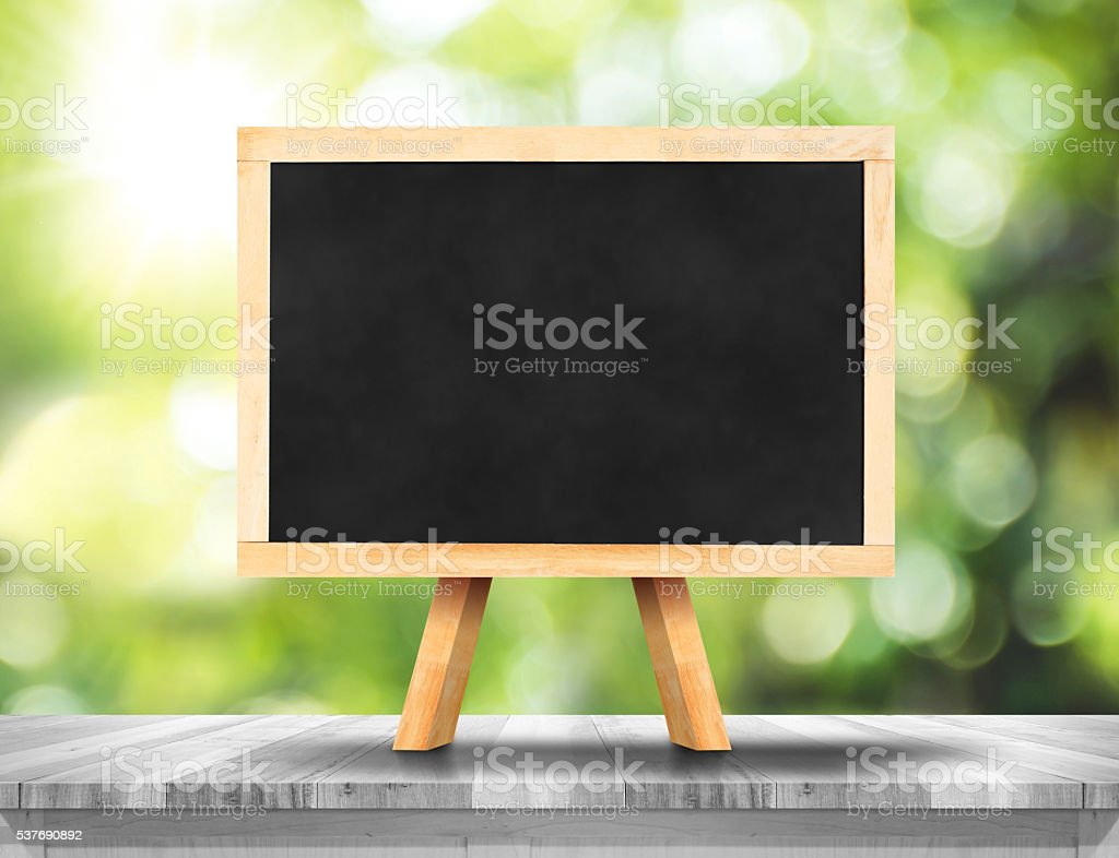 Blank blackboard on white wood table with sun stock photo