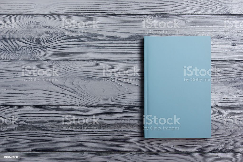 Blank book cover on textured wood background. Copy space stock photo