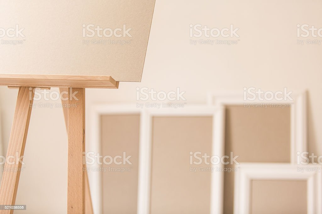 Blank canvas on easel and picture frames in artist's studio stock photo