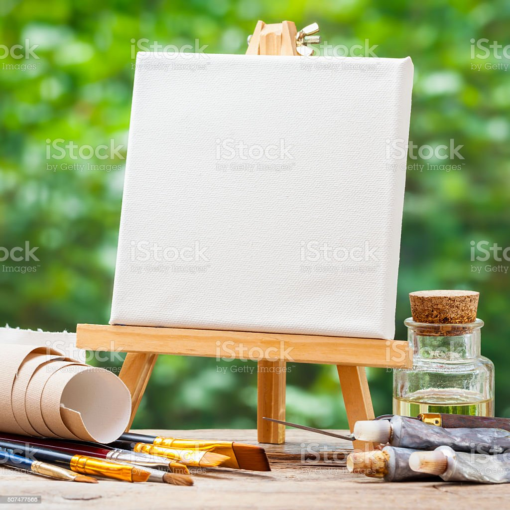 Blank canvas on easel, artistic paintbrushes, tubes of oil paint stock photo