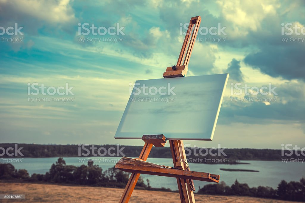 Blank canvas rests on a easel on lake landscape stock photo