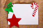 Blank card with christmas felt decorations on jute background.