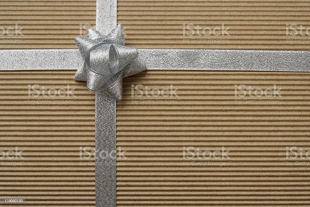 Blank cardboard gift box tied with a silver ribbon bow royalty-free stock photo