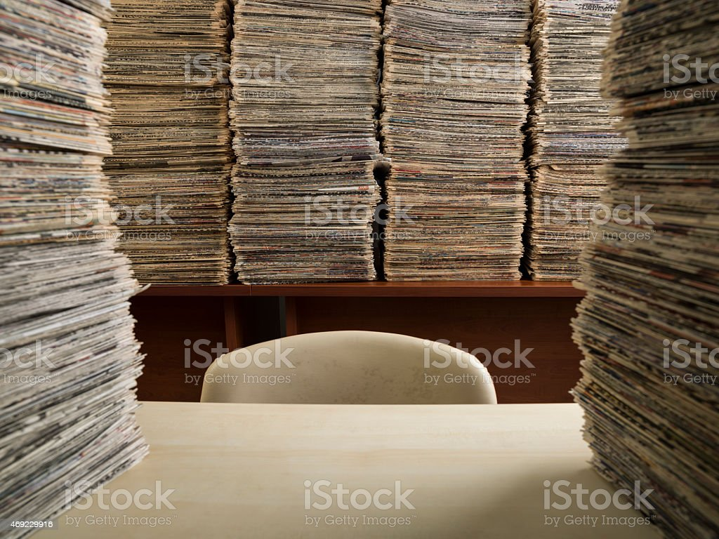 Blank chair and desk in library of media with newspapers stock photo