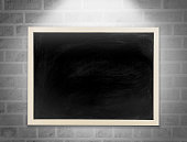 Blank chalkboard, blackboard hanging on the white brick wall