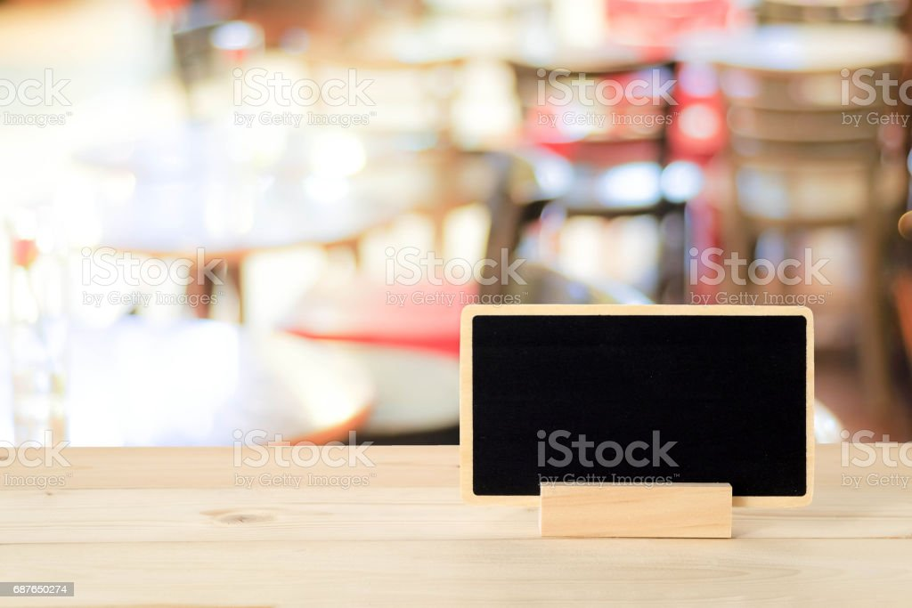 Blank chalkboard standing on wood table over blur restaurant with bokeh background, space for text, mock up, product display montage stock photo