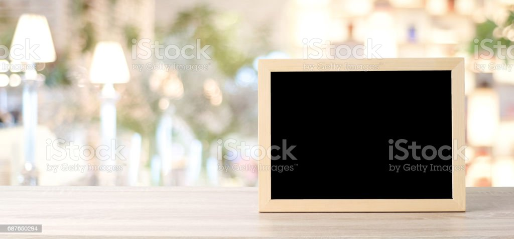 Blank chalkboard standing on wood table over blur restaurant with bokeh background, space for text, mock up, product display montage, banner stock photo