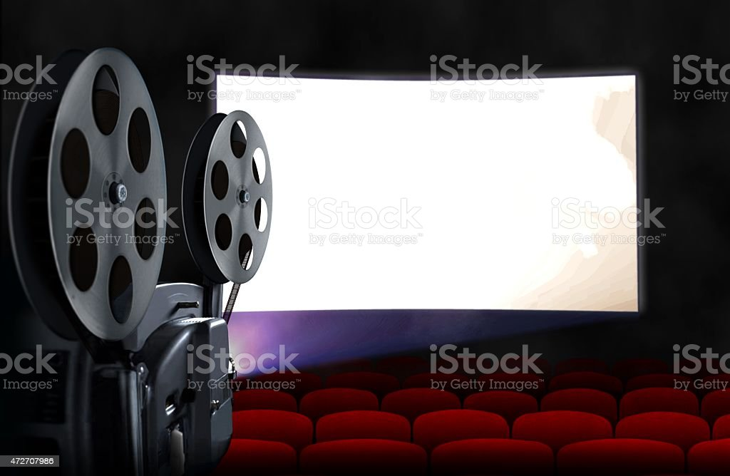 Blank cinema screen with empty seats and projector stock photo