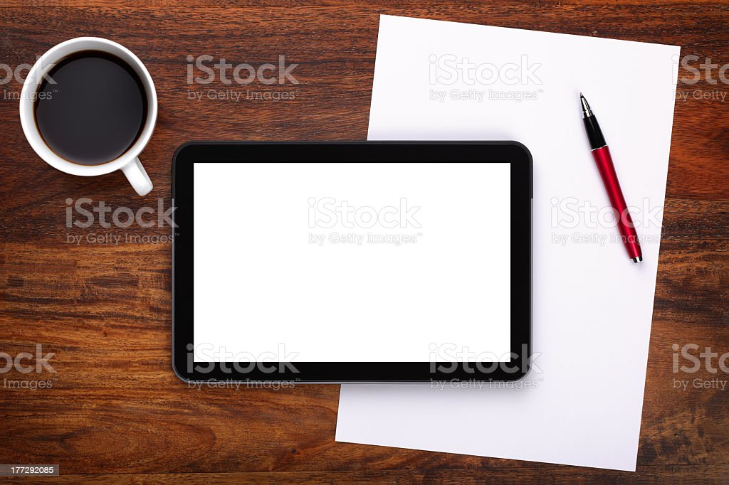 A blank digital tablet, coffee, pen and paper on a desk royalty-free stock photo