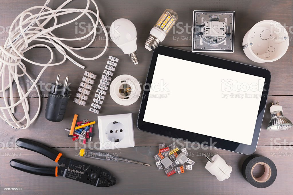 blank digital tablet with electrical tools and equipment on gray...