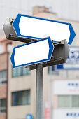 Blank direction signpost in city background.