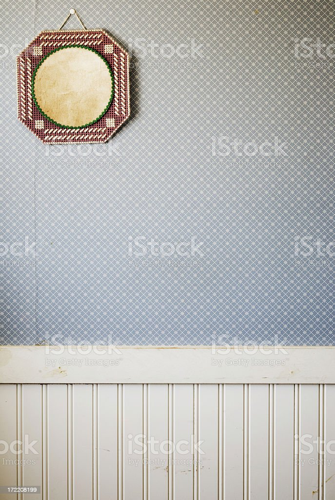 Blank embroidered frame on wallpapered wall stock photo