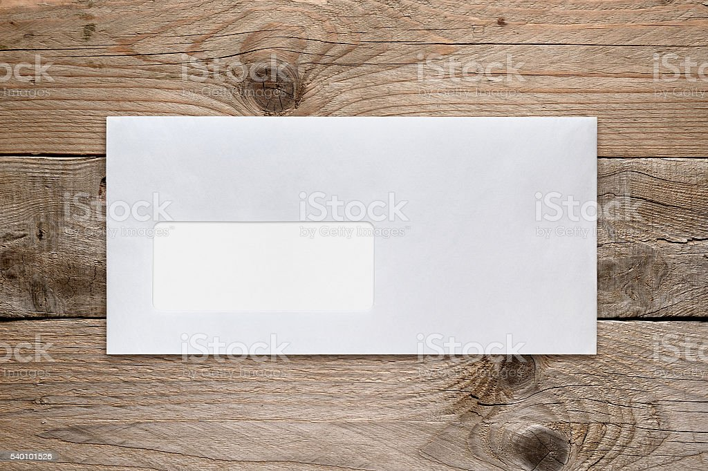 Blank envelope with address window on wooden table stock photo