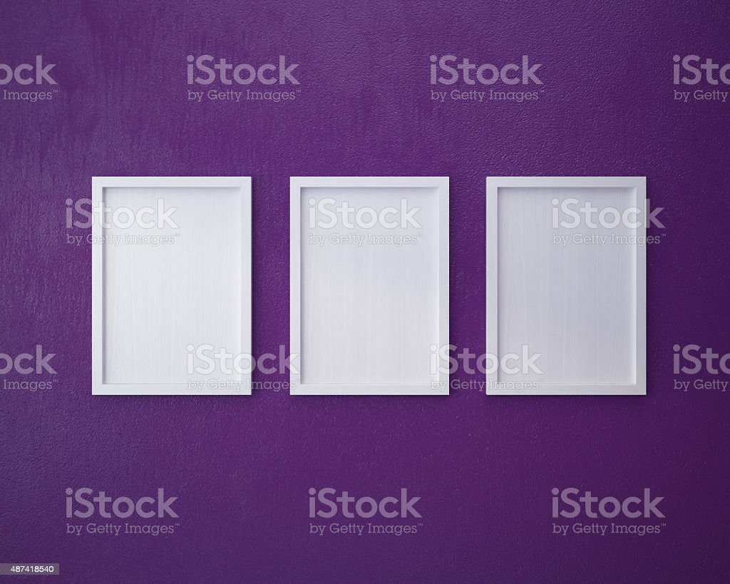 3 Blank frame on  purple wall. stock photo
