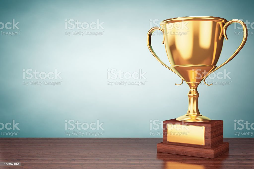 Blank gold cup trophy on wooden table stock photo