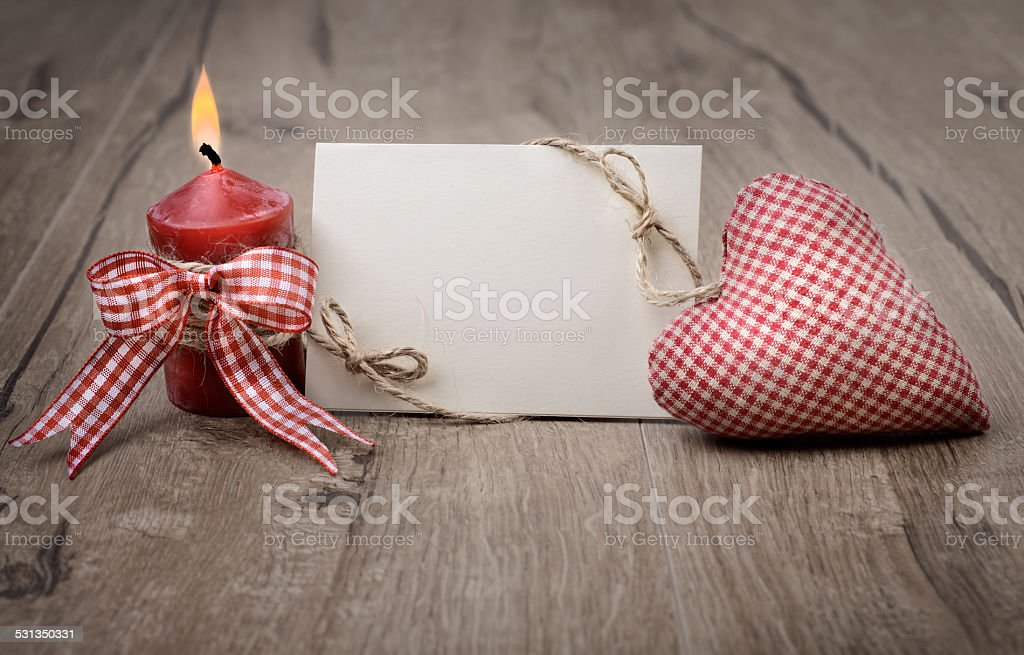 Blank greeting card with burning candle and stuffed heart stock photo