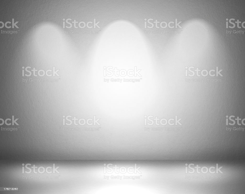 Blank grey wall with three evenly space spotlights overhead stock photo