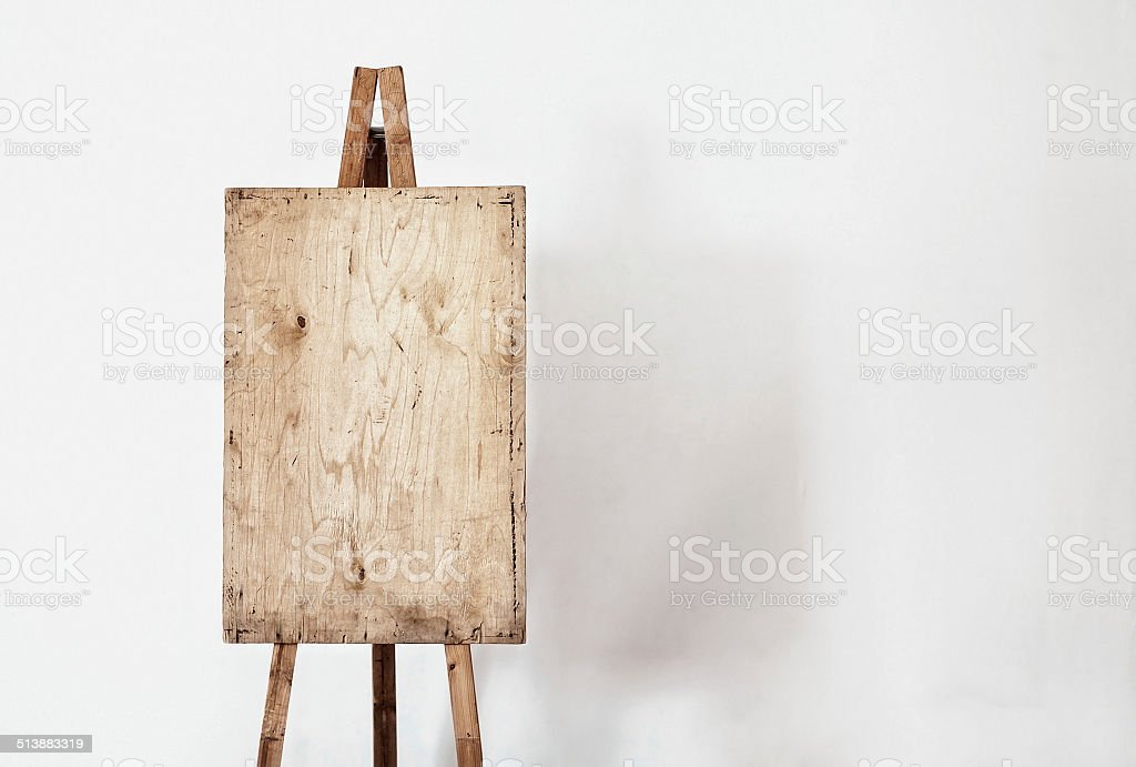 Blank grunge easel in a light room stock photo