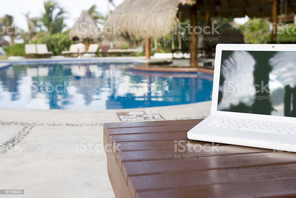 Blank Laptop on Bench by Empty Tropical Pool, Copy Space royalty-free stock photo
