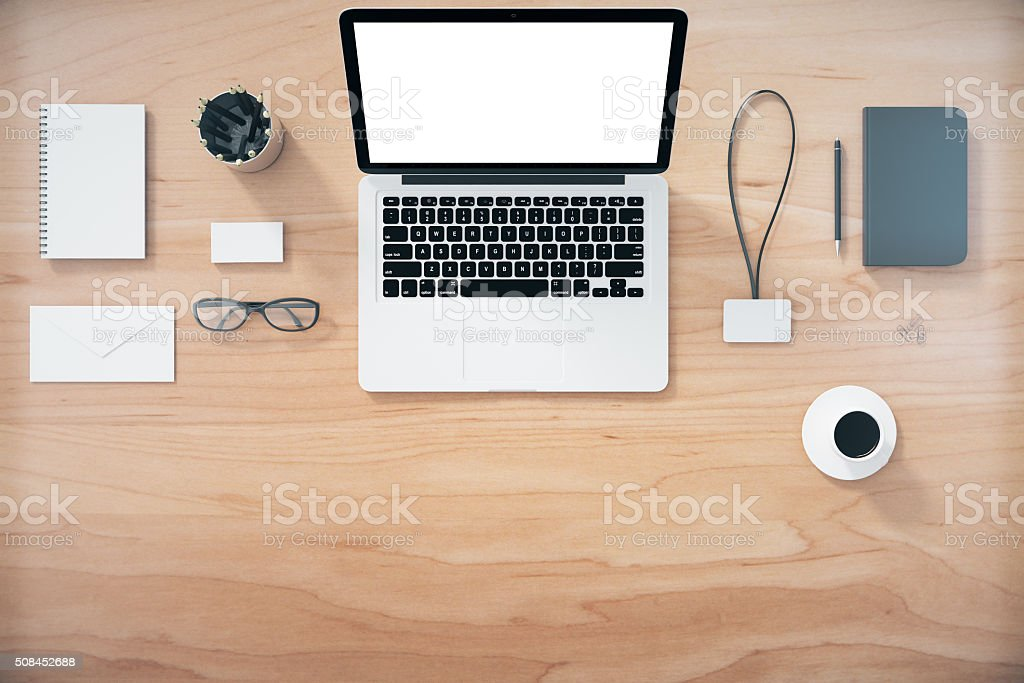 Blank laptop screen with office accessories on wooden table, moc stock photo