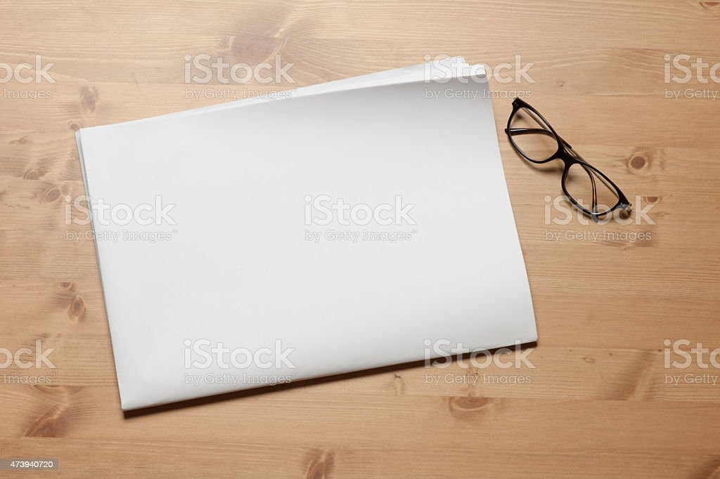 A blank newspaper on a wooden desk with black glasses near stock photo
