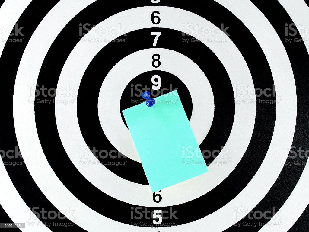 blank note with blue pushpin on center of dartboard stock photo