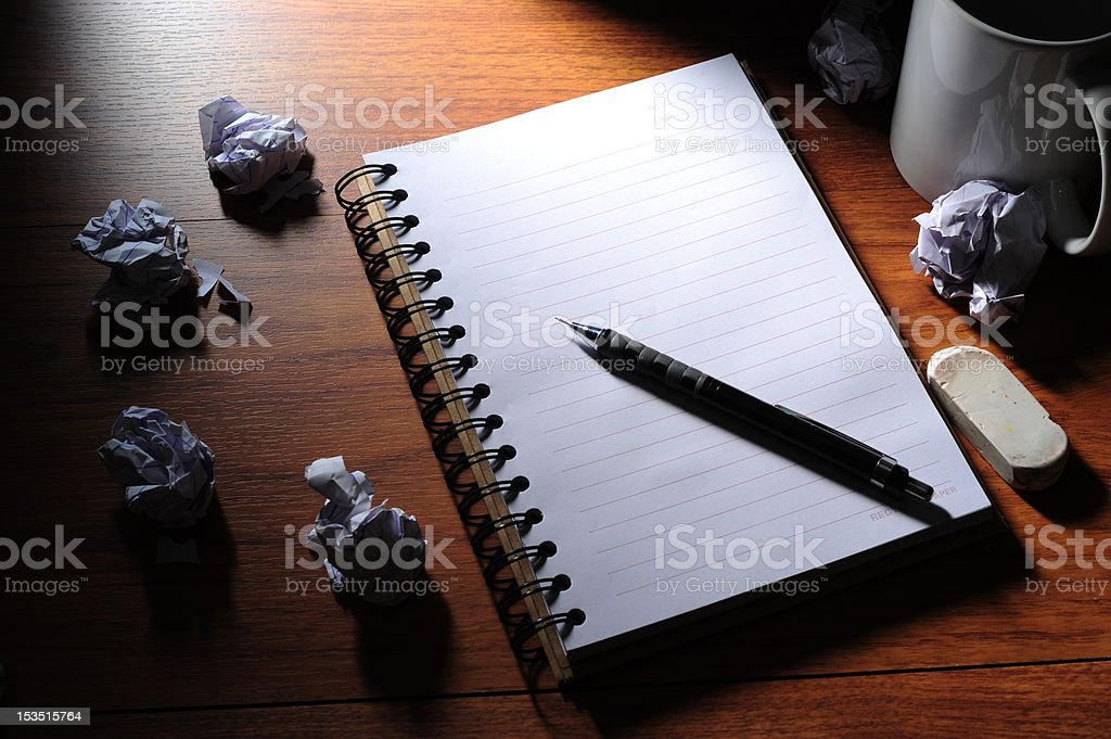 blank notebook, crumpled pieces of paper and a coffee mug royalty-free stock photo