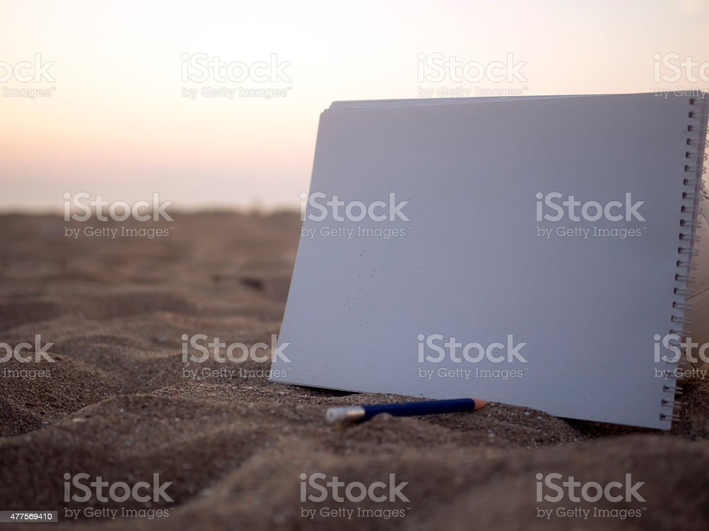 Blank notebook over sand stock photo