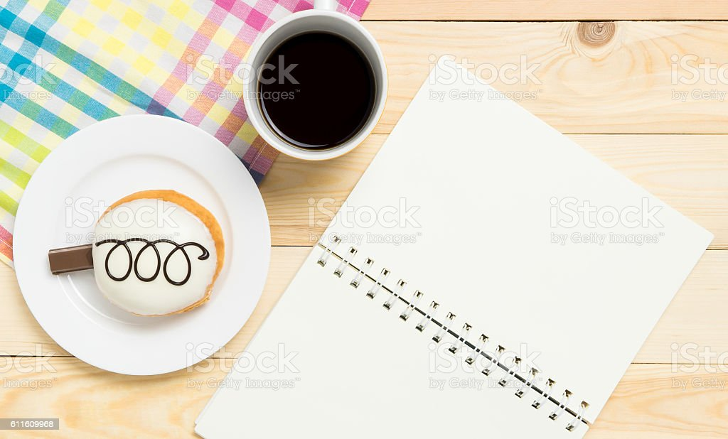 Blank notebook with donut and coffee in cafe stock photo