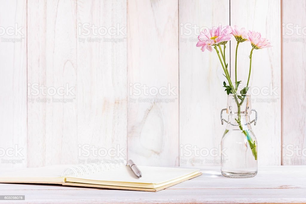 Blank notebook with flower on white wooden table stock photo