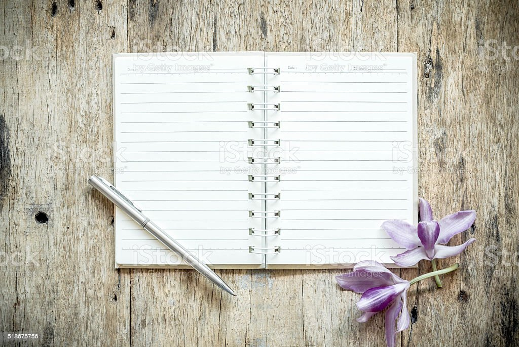 Blank notebook with orchids purple flowers on wooden table. stock photo