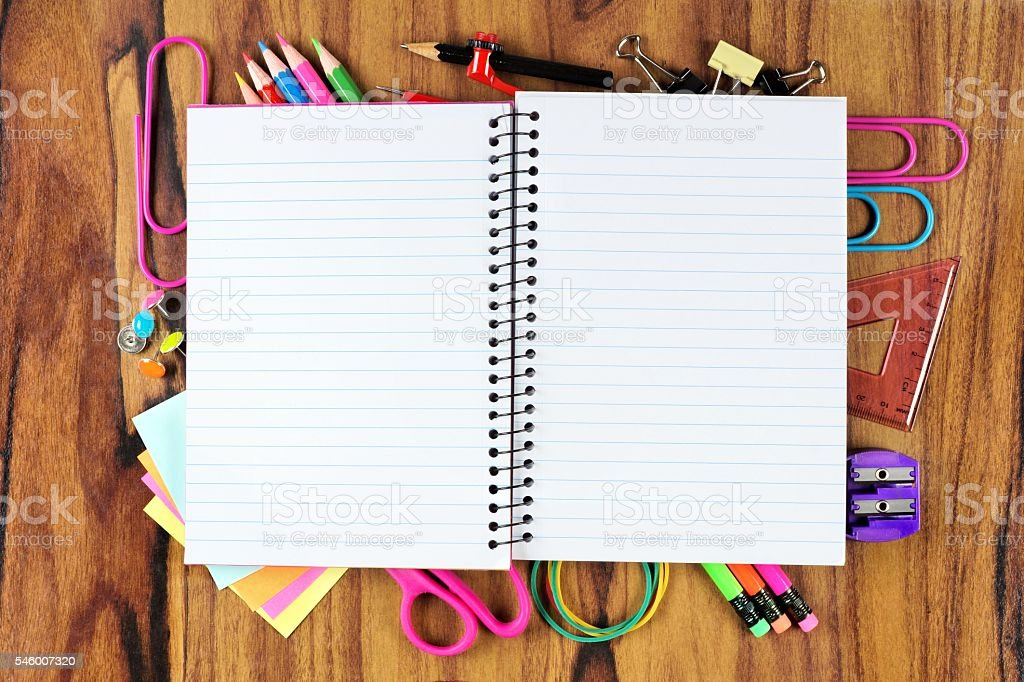 Blank notebook with underlying frame of school supplies over wood stock photo