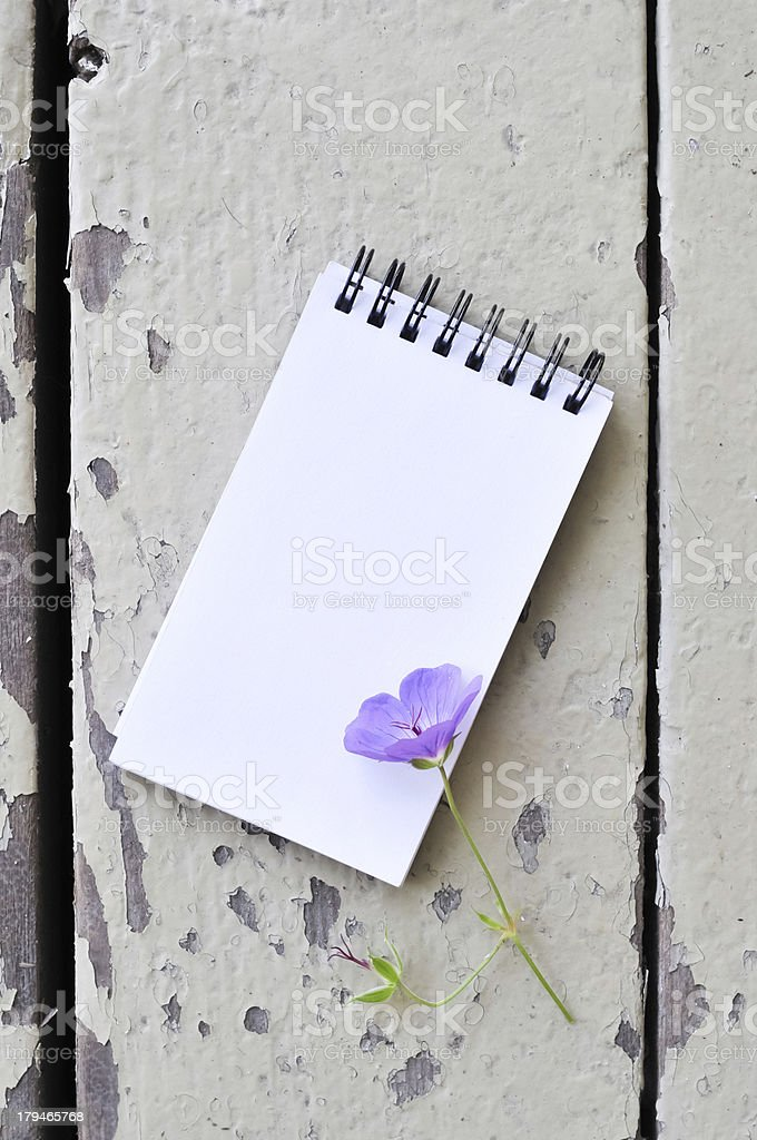 blank notepad and violet flower on plank wood background royalty-free stock photo