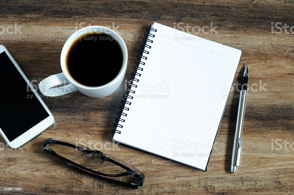 Blank notepad, eye glasses, coffee, pen and smart phone stock photo