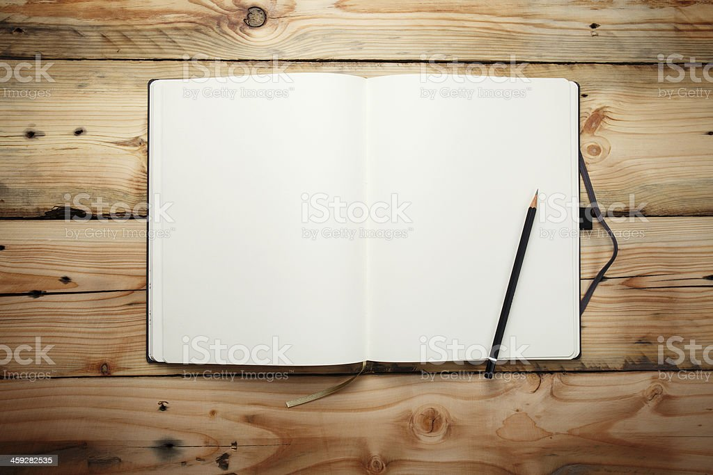 Blank notepad  with a pencil laying on old wooden table stock photo