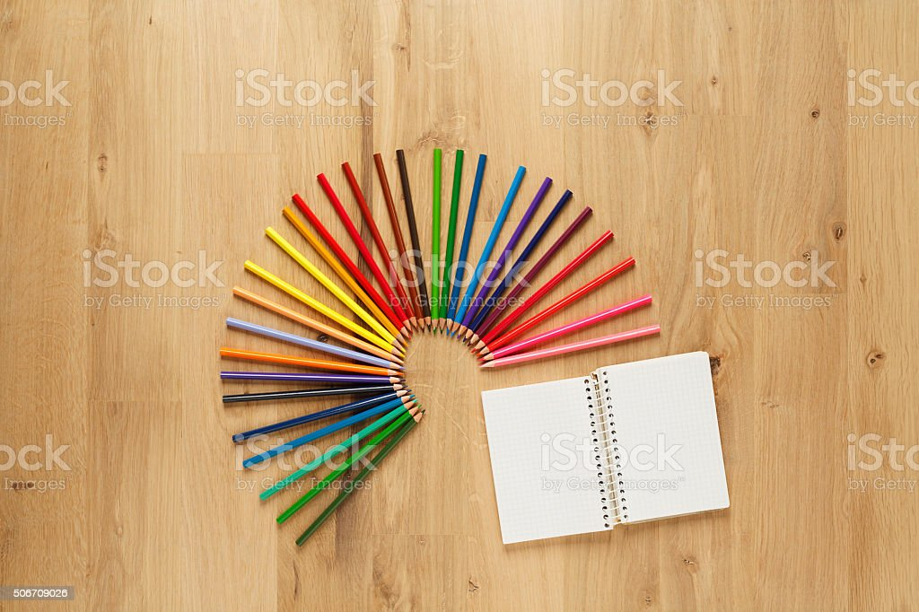 Blank notepad with  colored pencils on  wooden floor parquet background stock photo