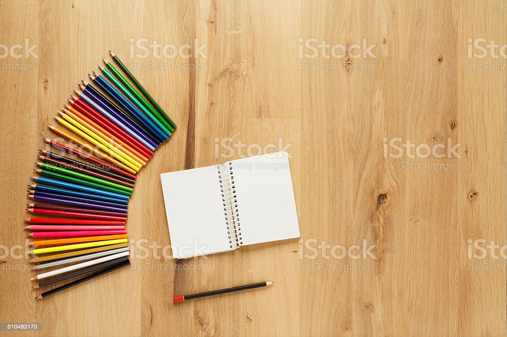 Blank notepad with  colored pencils on  wooden table background stock photo