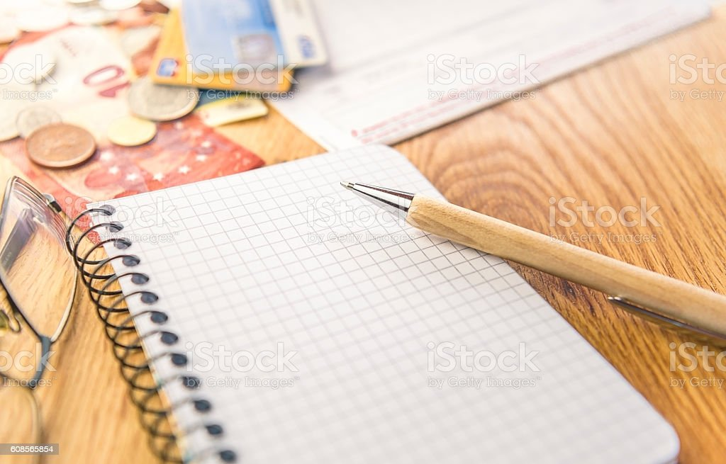 Blank notepad with pen and financial elements stock photo