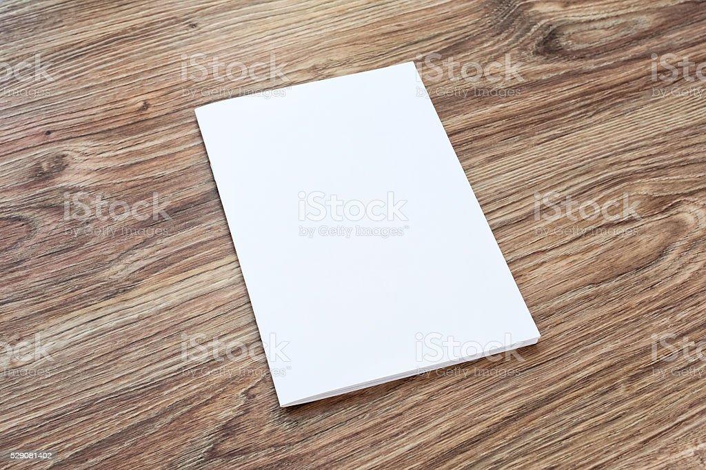Blank of brochure is on a wooden desk. stock photo