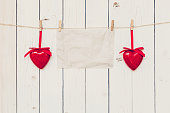 Blank old paper and red heart hanging on wood board