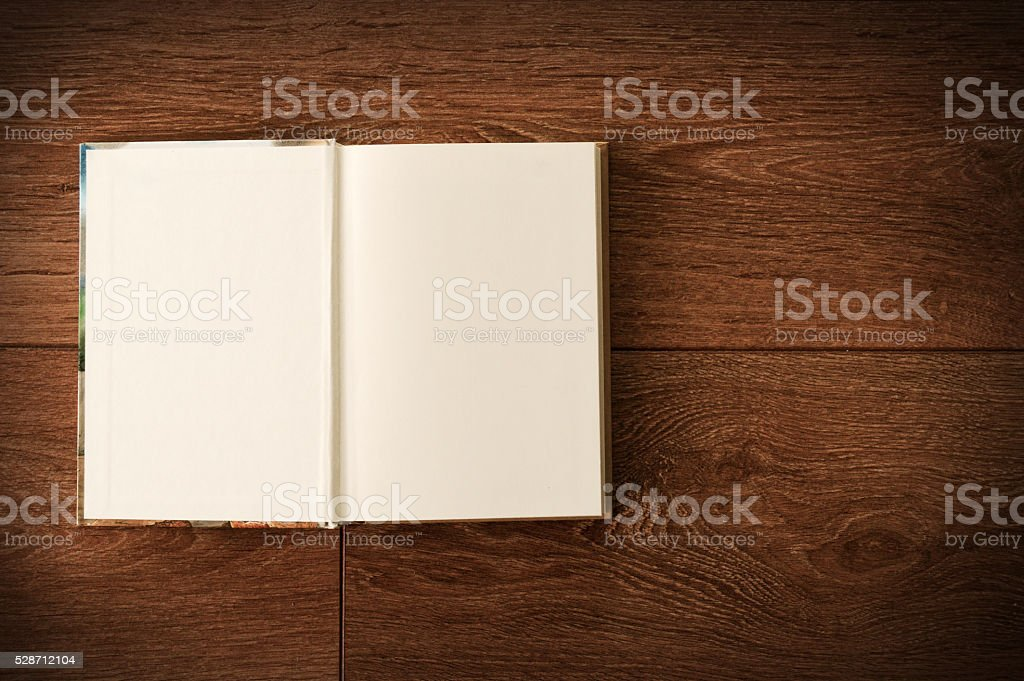 Blank open notebook on a dark wooden surface stock photo