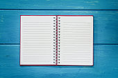 blank open notebook on blue wooden table