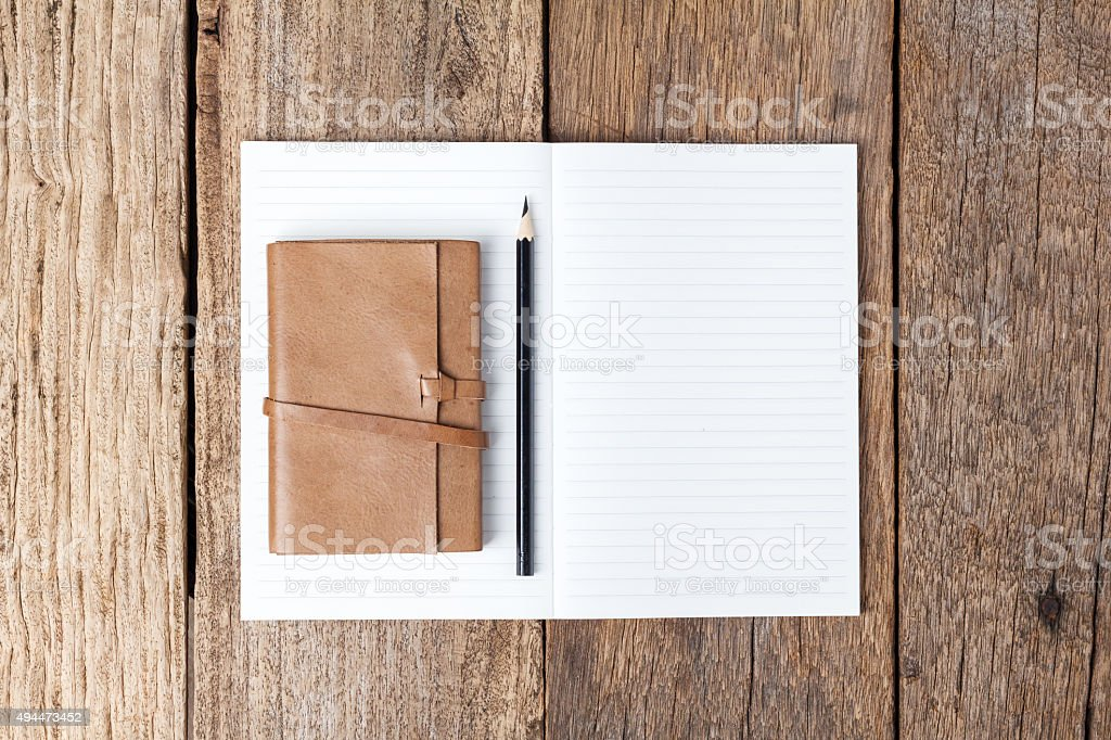 Blank open notebook with black pencil on wood table stock photo
