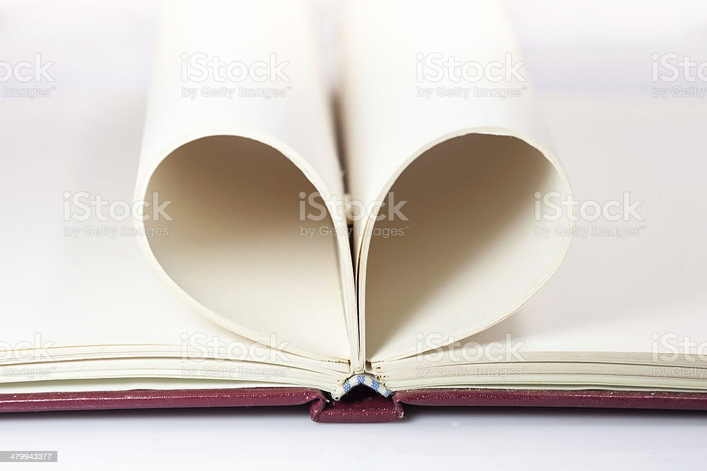 Blank opened notebook with sheets folded in form of  heart royalty-free stock photo