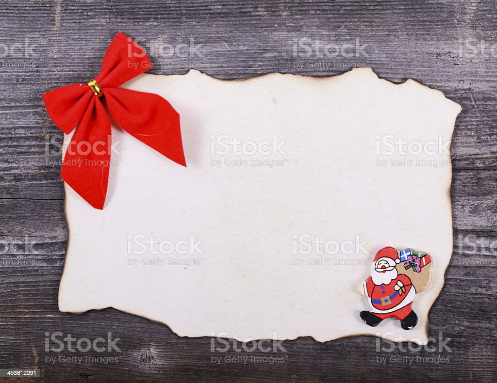 Blank paper againts wooden background with red bow royalty-free stock photo