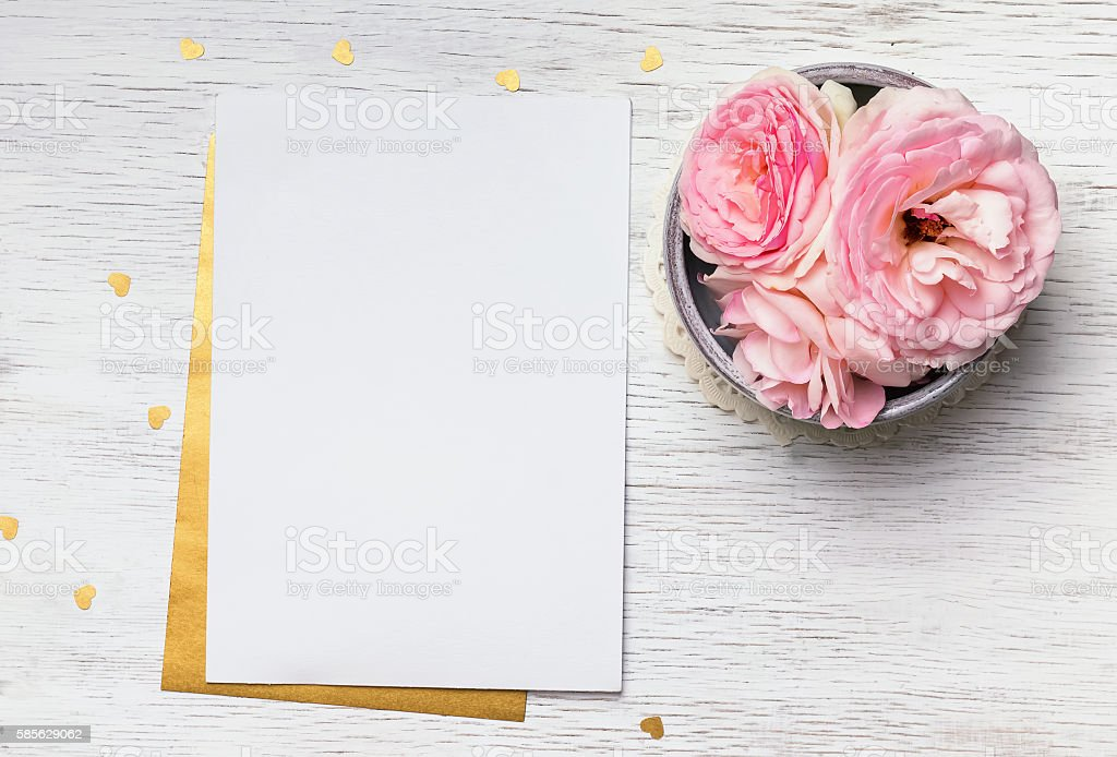 Blank paper and cute pink flowers on white wooden table stock photo