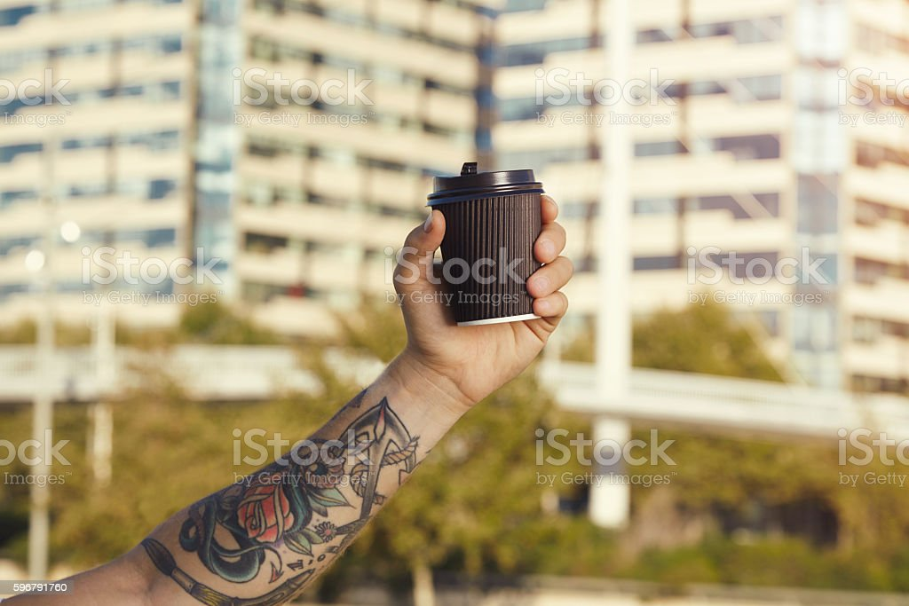 Blank paper coffee cup in tattooed man's hand stock photo