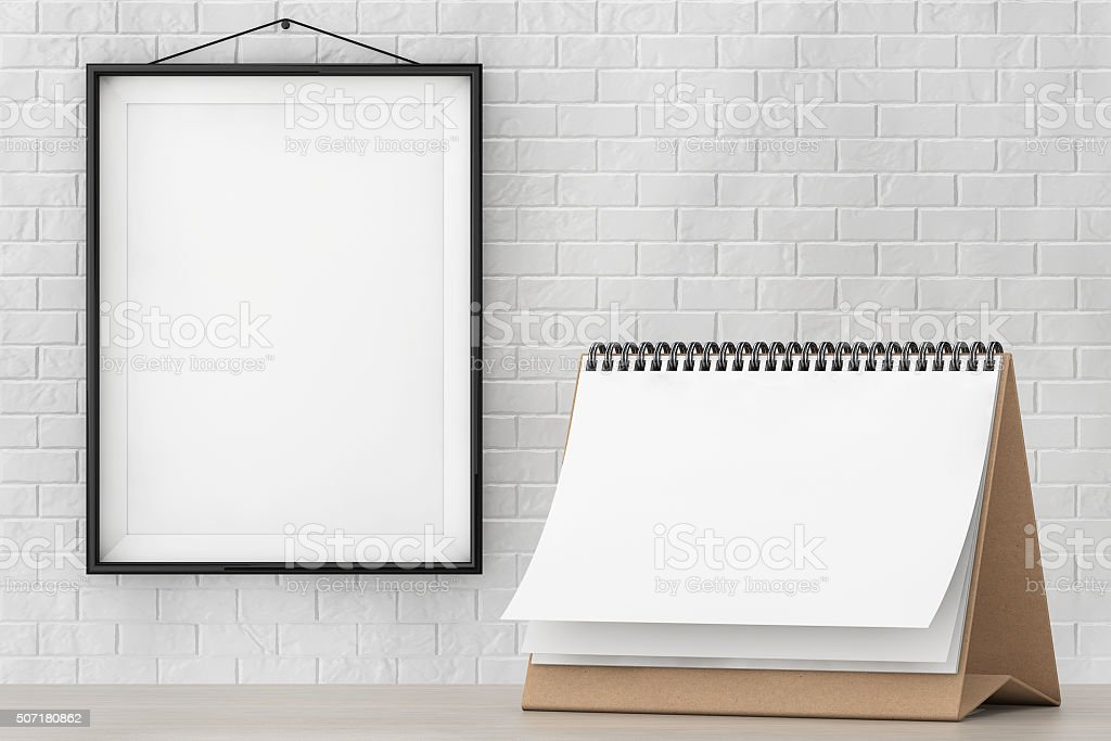 Blank Paper Desk Spiral Calendar in front of Brick Wall stock photo