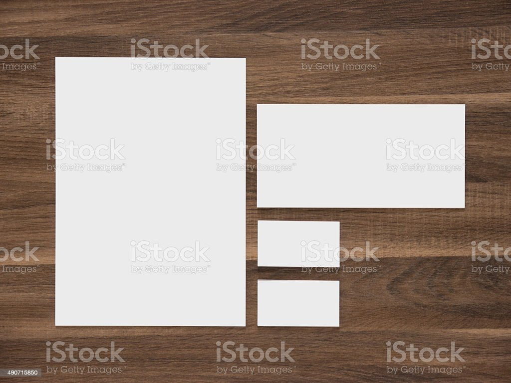 Blank paper, envelope and business cards on wooden background stock photo