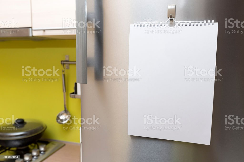 blank paper sheet hanging on fridge door stock photo